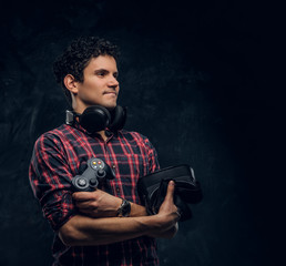 Handsome gamer holding VR headset, headphones and console joystick in a studio against the background of the dark wall