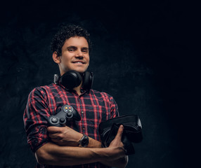 Cheerful gamer holding VR headset, headphones and console joystick in a studio against the background of the dark wall