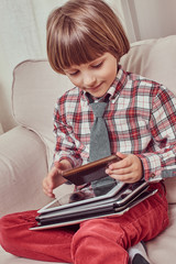Cute schoolboy wearing a checkered shirt sitting on a couch with set of tablets at home