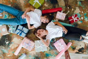 Two girls, best friends lying on the floor among colorful present boxes. Birthday girt concept. Packing presents. Giveaway. Top view