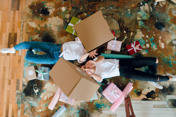 Two girls, best friends thowing gift boxes in the air while lying on the floor among colorful present boxes. Birthday girt concept. Packing presents. Giveaway