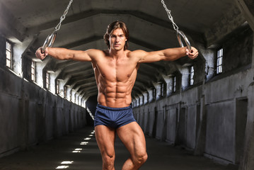 A handsome athlete with muscular body posing with gymnastics rings in the abandoned industrial building