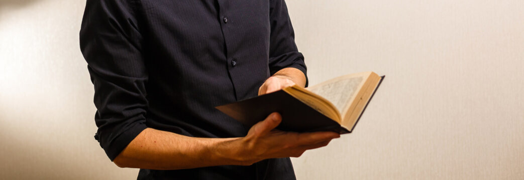 Missionary man holds his bible with interlocked fingers to pray.