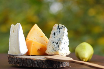 Cheese and pear on wooden boards. Various cheese on natural blurred background. Dorblu, camembert and hard yellow cheese on parchment paper