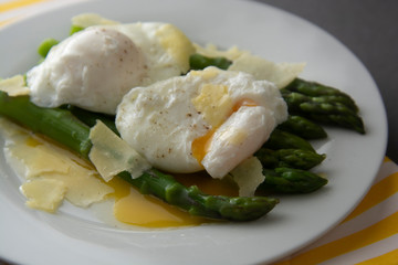 Close up asparagus salad with poached egg and parmesan cheese. Gray background. Healthy, tasty breakfast.