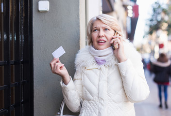 Mature woman is asking about address by phone in time walking