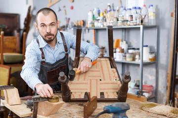 Carpenter repairing antique chair