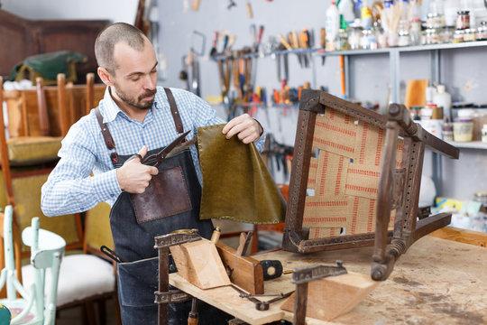 Craftsman reupholstering chair in workshop