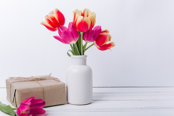 Mother's day composition.Vase with tulips and gifts