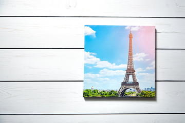 Canvas print. Photo with gallery wrap method of canvas stretching on stretcher bar. Photography with image of  The Eiffel Tower (Paris, France) hanging on a white wooden wall