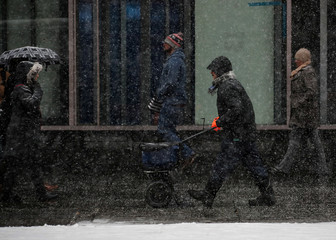 A worker spreads salt on a sidewalk during a winter snow storm in New York