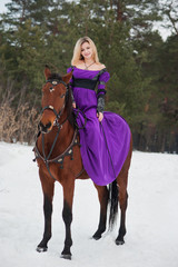 Beautiful girl in historical clothes riding a horse