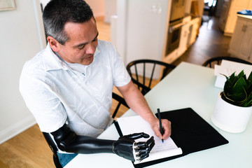 Man rests his robotic arm on table and writes in ledger