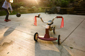 Girl with ball and tricycle in driveway