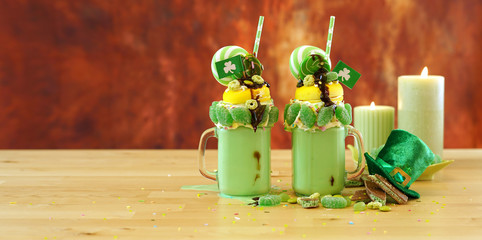 Happy St Patrick's Day on-trend holiday freak shakes milkshakes decorated with candy and lollipops, web size banner with copy space.