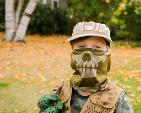 Portrait of cute boy wearing army soldier costume while standing on grassy field in park