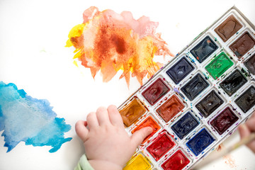 little girl bedaubed with bright colors Multicolored watercolor in small hands. Blot on white background