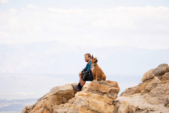 Side view of man with dog looking away while sitting on rock against cloudy sky