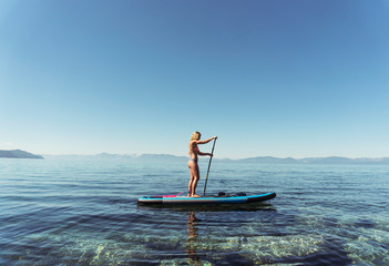 Side view of woman in bikini paddleboarding on lake against clear blue sky during sunny day