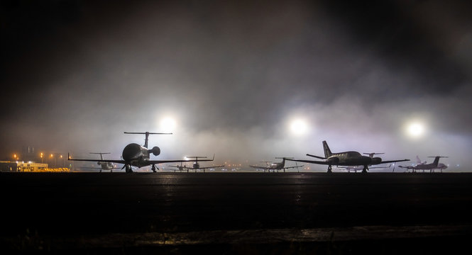 small aviation,the dark view of silhoete private jet on airport. Lights in the background