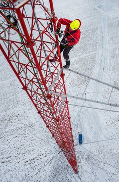 Worker climbing up on red industrial construction use safety harness, irata worker, rope access