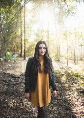 Portrait of teenage girl with long hair standing against trees in forest
