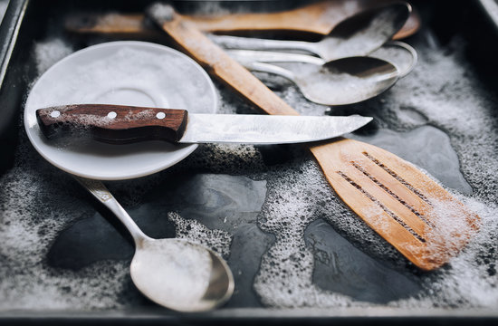 Washing dishes concept. A plate, a knife, wooden kitchen spatulas and spoons in the detergent foam on a black oven-tray.