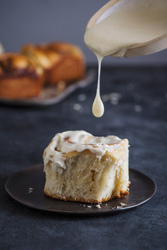 Close up of cream pouring on cinnamon bun on plate