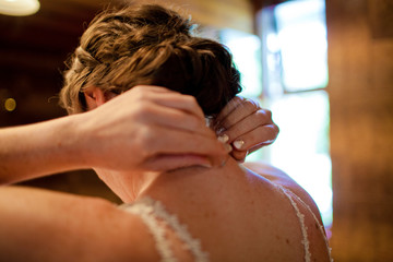 Rear view of bride wearing necklace while standing at home