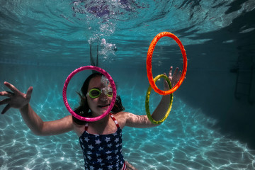 Smiling girl wearing swimming goggles while playing with colorful rings in pool
