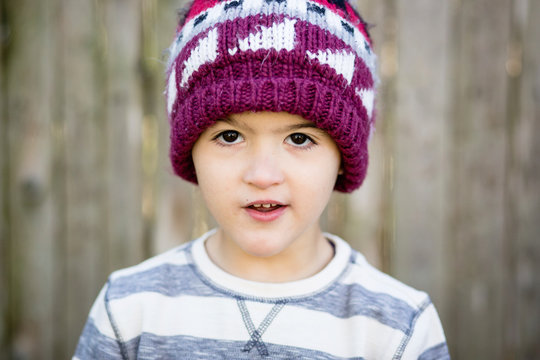 Close-up portrait of cute boy wearing knit hat while standing against fence in yard