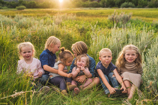 Friends sitting in grassy field during sunset