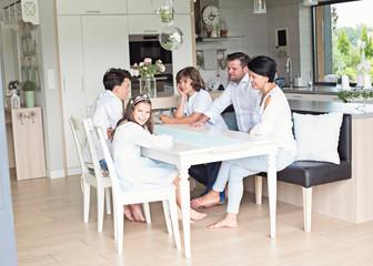 Fototapeta  Family Eating Meal Around Kitchen Table Together  obraz