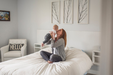 Mother kissing son on bed at home