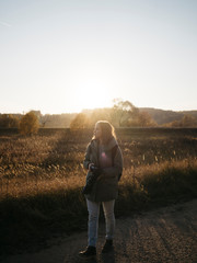 Woman with camera standing on field against clear sky during sunset