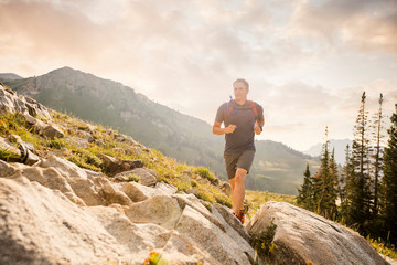 Confident male hiker running on mountain against cloudy sky