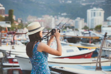 Side view of woman wearing hat photographing boats moored at harbor with camera while standing in town