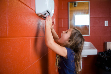 Side view of cute girl screaming over hand dryer while standing against wall in bathroom