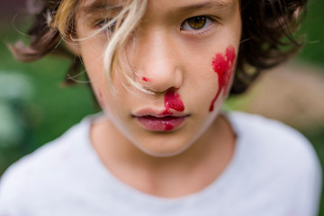 Close-up portrait of cute boy with red face paint standing in park