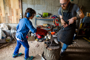 Blacksmith teaching boy to use hammer on anvil in workshop