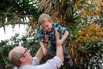 Playful father lifting cute cheerful son against branches in park
