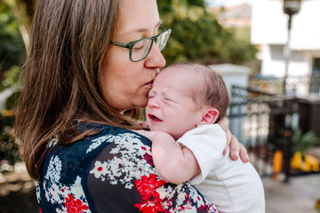 Close-up of mother kissing cute newborn son on balcony