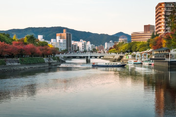 Hiroshima Riverscape at sunset  in Japan with the Peace Memorial Park on the left hand side and ruin of the Atomic Bomb Dome in the background.