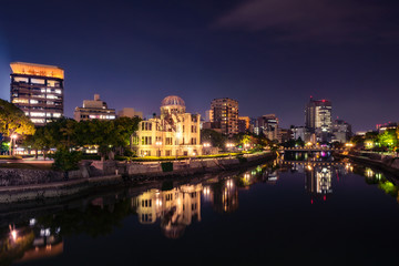 Hiroshima Skyline by night on the side of Motoyasu river in Japan with the Atomic Bomb Dome, the historic remains of the atomic blast.