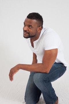 Happy black man kneeling in a white shirt