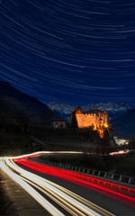 Beautiful view of Italian castle with trails of stars and car lights - snow covered Alps in background
