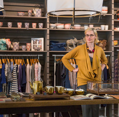 Portrait of female owner with blond hair standing in shop