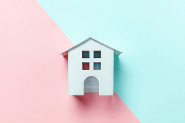Simply design with miniature white toy house isolated on blue pink pastel colorful trendy geometric background. Mortgage property insurance dream home concept. Flat lay top view copy space