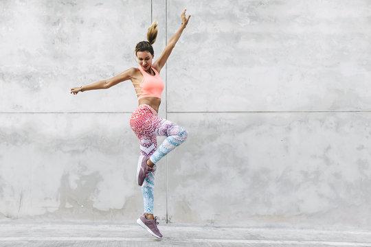 Dancer in fashion sportswear jumping over gray wall