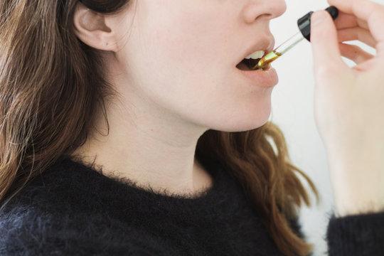 Woman Ingesting Oil Under Tongue